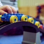 Das Bild zeigt eine Kinderhand, die einen Lego-Zug über eine Brücke fahren lässt.