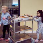 Das Bild zeigt zwei Mädchen, die den Wagen mit dem Mittagessen holen.