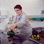 Das Bild zeigt eine Mitarbeiterin beim Polieren einer Motorhaube.