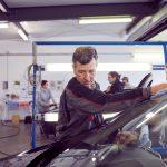 Das Bild zeigt einen Mitarbeiter beim Reinigen der Windschutzscheibe eines Fahrzeugs.