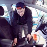 Das Bild zeigt einen Mitarbeiter bei der Innenreinigung eines Fahrzeugs.