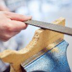 Das Bild zeigt in Nahaufnahme, wie ein Mitarbeiter ein Stück Holz abfeilt.