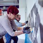 Das Bild zeigt einene Mitarbeiterin und einen Mitarbeiter beim Anfertigen eines Wandmosaiks.