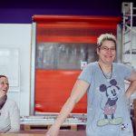 Das Bild zeigt Leiterin Heike Guthardt und eine lachende Mitarbeiterin mit einem Micky-Maus-T-Shirt.