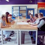 Das Bild zeigt sechs Menschen an einem Tisch, die gemeinsam etwas planen.