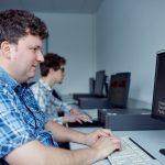 Das Bild zeigt zwei Mitarbeiter im Computerraum.