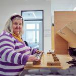 Das Bild zeigt eine Mitarbeiterin beim Montieren von Werkstücken.