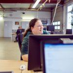 Das Bild zeigt eine Mitarbeiterin am PC.