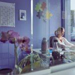 Das Bild zeigt durch eine Glasscheibe den Blick in das Büro der Leiterin Frau Guthardt, die am Schreibtisch sitzt.