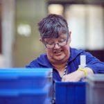 Das Bild zeigt eine Mitarbeiterin beim Sortieren.