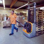 Das Bild zeigt einen Mitarbeiter, der ein Transportgerät mit Holzpaletten führt.