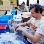 Das Bild zeigt einen Mitarbeiter bei Verpackungstätigkeiten.