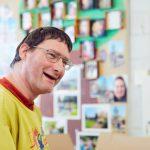 Das Bild zeigt einen lachenden Mitarbeiter vor einer Wand mit bunten Postkarten.