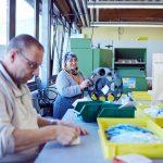 Das Bild zeigt Mitarbeiter beim Sortieren von Werkstücken.