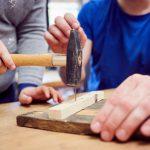 Das Bild zeigt, wie ein Nagel mit einem Hammer in ein Stück Holz getrieben wird.