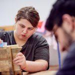 Das Bild zeigt eine Mitarbeiterin, die ein Stück Holz abschleift.