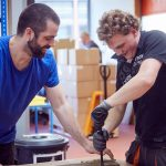 Das Bild zeigt einen Betreuer und einen Mitarbeiter bei der Arbeit mit Holz.
