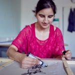 Das Bild zeigt eine junge Frau, die mit Textilfarbe arbeitet.