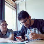 Das Bild zeigt zwei Mitarbeiter, die an einem Schriftstück arbeiten.