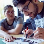 Das Bild zeigt einen Mitarbeiter, der ein Schriftstück gestaltet.