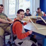 Das Bild zeigt einen Mitarbeiter, der einen fertigen Holzrahmen hält.