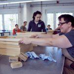 Das Bild zeigt eine Mitarbeiterin der Schreinerei, die Holzrahmen bearbeitet.