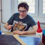 Das Bild zeigt einen Mitarbeiter, der einen Holzrahmen anfertigt.