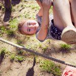 Das Bild zeigt ein Mädchen, das an einem Seil turnt.