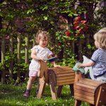 Das Bild zeigt Kinder, die auf dem Außengelände mit Holzpferden spielen.