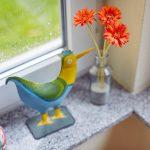 Das Bild zeigt einen bunten Metallvogel und eine Blumenvase auf einer Fensterbank.