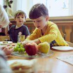 Das Bild zeigt Kinder, die am Tisch Obst essen.