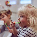 Das Bild zeigt zwei Kinder beim Zähneputzen.