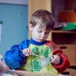 Das Bild zeigt einen Jungen, der eine Plastikflasche bemalt.