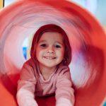 Das Bild zeigt ein Mädchen in einem Plastiktunnel beim Turnen.