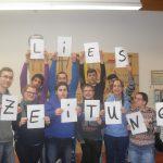 """Das Bild zeigt elf Menschen, die Blätter mit Buchstaben hochhalten, die den Satz """"Lies Zeitung"""" ergeben."""
