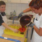 Das Bild zeigt zwei Frauen beim Abfüllen von Marmelade.