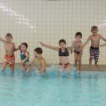 Das Bild zeigt sieben Kinder, die vom Rand ins Schwimmbecken springen.
