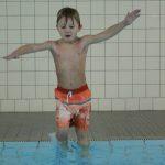 Das Bild zeigt ein Kind, das vom Rand ins Schwimmbecken springt.