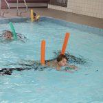 Das Bild zeigt zwei Kinder beim Schwimmen mit einer Poolnudel