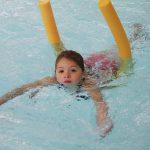 Das Bild zeigt ein Kind beim Schwimmen mit einer Poolnudel.