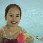 Das Bild zeigt ein Mädchen im Schwimmbad mit einem bunten Ball.