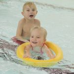 Das Bild zeigt zwei Kinder beim Schwimmen.