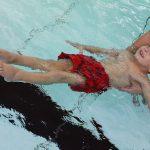Das Bild zeigt einen Jungen beim Rückenschwimmen.