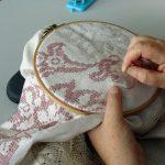Das Bild zeigt in Nahaufnahme zwei Hände, die mit einer Stickarbeit beschäftigt sind.