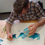 Das Bild zeigt, wie ein Mitarbeiter das Bild eines Sportwagens malt.
