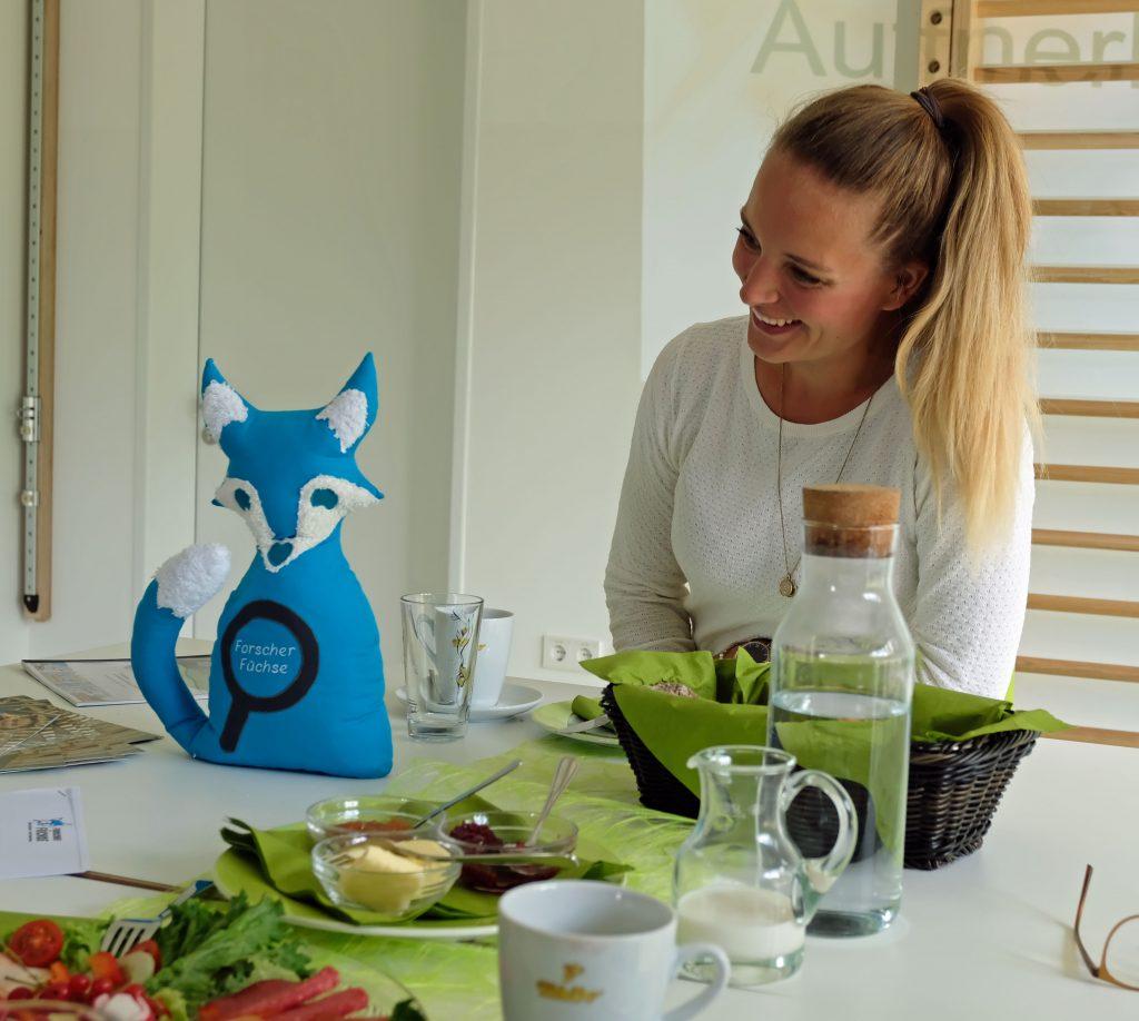 """Das Bild zeigt Kita-Leiterin Sina Caspers mit einem """"Forscher-Fuchs"""" aus Filz."""