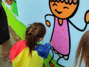 Das Bild zeigt ein Kind, das eine Mauer bemalt.
