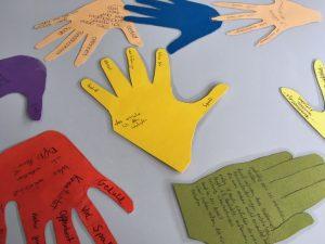 Das Bild zeigt Handumrisse aus buntem Papier, die mit Wünschen beschriftet sind