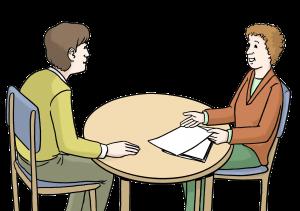 Sie sehen zwei Menschen an einem Tisch. Der eine berät den anderen.