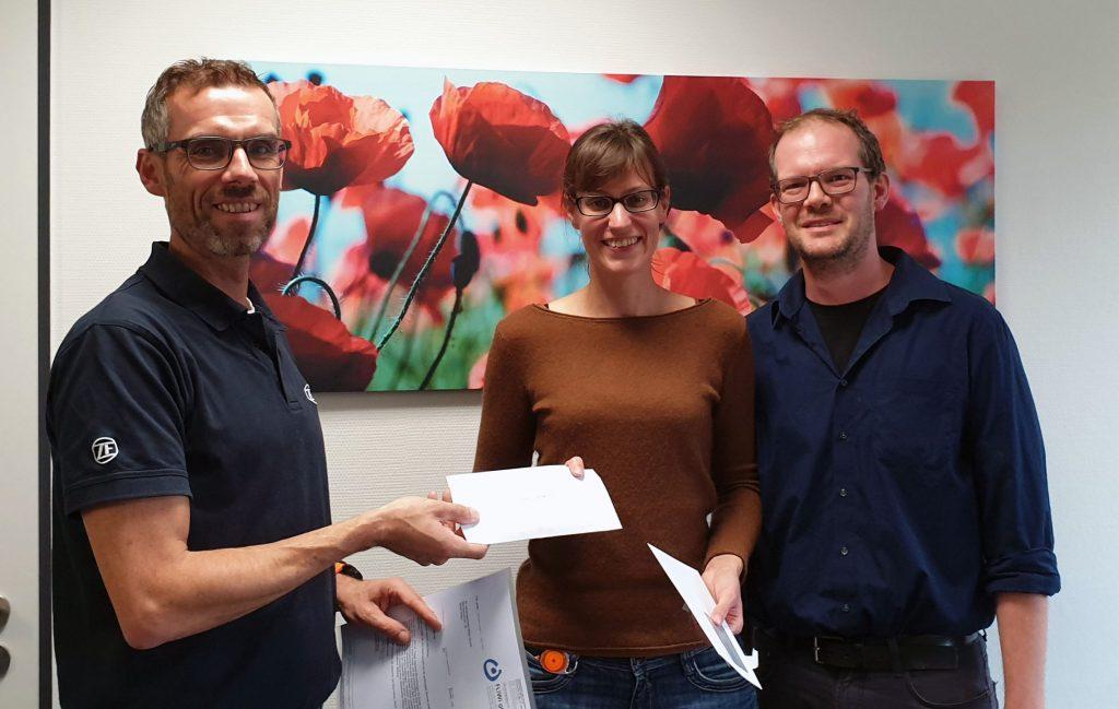 Auf dem Bild ist zu sehen, wie Frank Blasey von der Firma ZF den Spendenscheck an Christina Dronski und Roland Sauer übergibt.